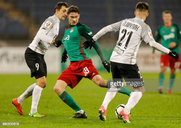 Rustem Mukhametshin and Vagiz Galiulin of FC Tosno vie for the ball with Aleksei Miranchuk of FC Lokomotiv Moscow during the Russian Football League...