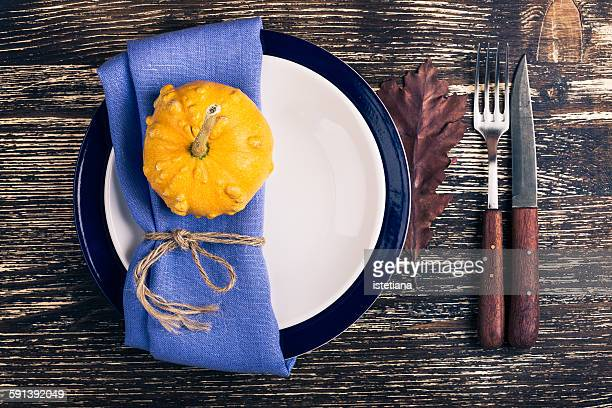 Rustic autumn place setting with miniature pumpkin