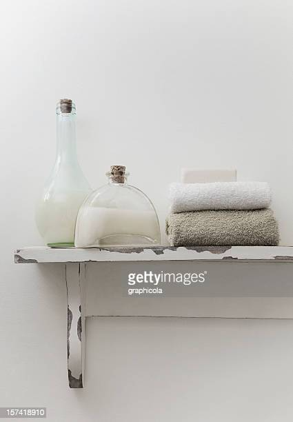 Rustic bathroom shelf with skincare products, towels and soap
