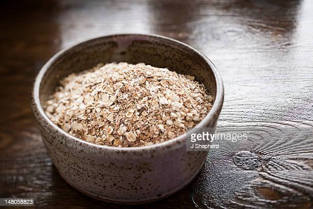 A rustic bowl of uncooked porridge oats (oatmeal)