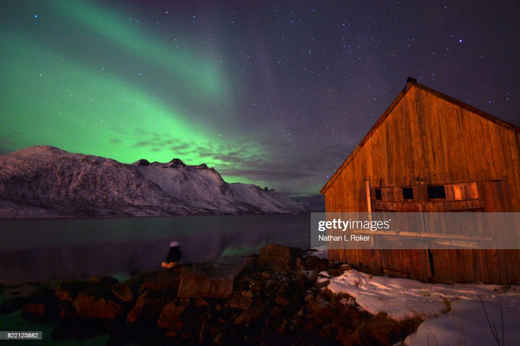 A rustic cabin retreat overlooked by a norwegian fjord and the northern lights : Stock Photo