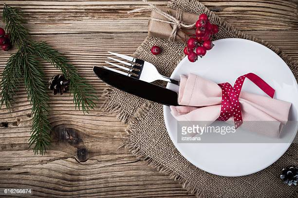 Rustic Christmas place setting,  plate, knife and fork wrapped with napkin on rustic wooden table, top view. Winter holiday theme,  Happy New Year decoration with copy space
