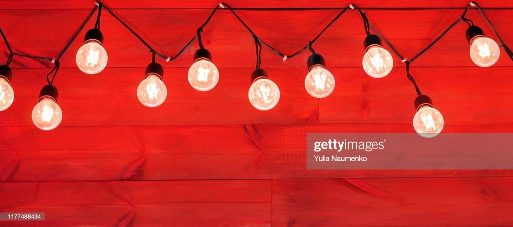 Rustic decorative Christmas background. Garland light on wooden red wall. Bright winter holiday banner with copy space to place text.Traditional decoration backdrop. : Stock Photo