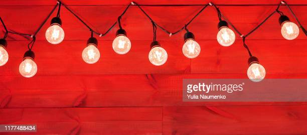 rustic decorative christmas background. garland light on wooden red wall. bright winter holiday banner with copy space to place text.traditional decoration backdrop. - country christmas stock pictures, royalty-free photos & images