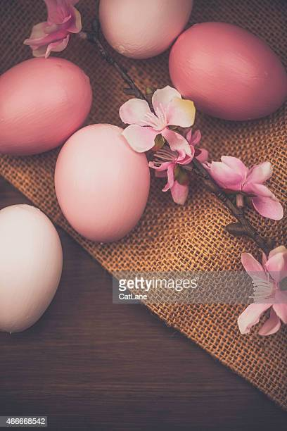 Rustic Easter still life. Pink eggs and blossoms. Wood background.