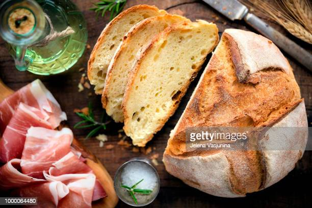 Rustic loaf of homemade bread served with olive oil, rosemary and cured ham on dark wooden table....