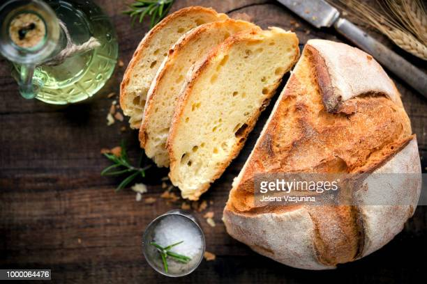 Rustic loaf of homemade bread served with olive oil, rosemary and salt on dark wooden table....