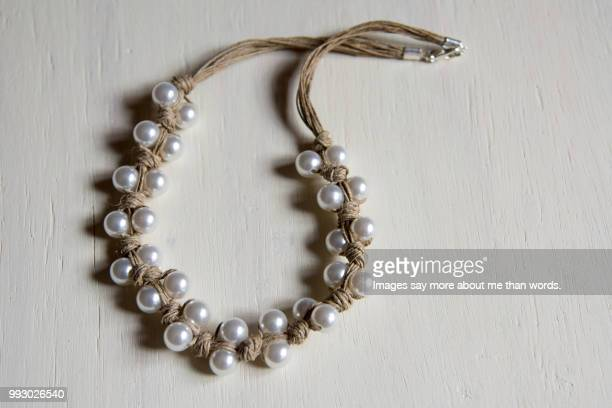 A rustic pearl necklace on a white background.