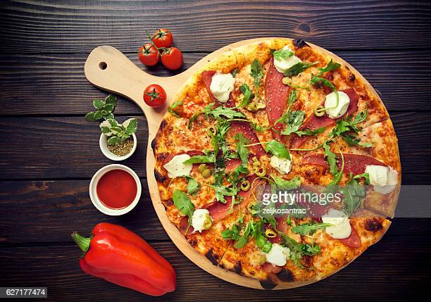 Rustic pizza with salami, olives and basil on wooden table