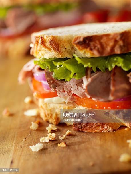Rustic roast beef sandwich on wooden cutting board