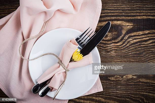 Rustic romantic place setting,  plate and utencils with pink napkin decoration with copy space, top view