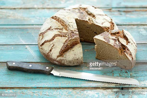 Rustic rye bread on blue wood, knife