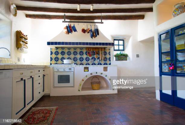 rustic southwest usa kitchen: brick floor, beams, oven, counters - mexican culture stock pictures, royalty-free photos & images