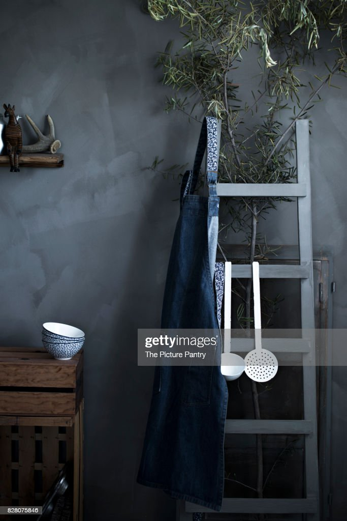 A rustic vintage kitchen with bowls, apron and utensils on a gray background : Stock-Foto