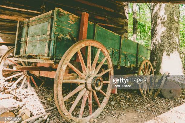 rustic wagon beside log cabin - cart stock pictures, royalty-free photos & images