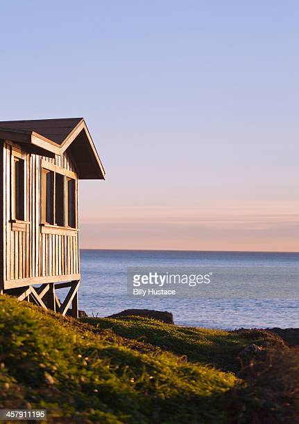 Rustic wooden cabin and Pacific Ocean at sunset