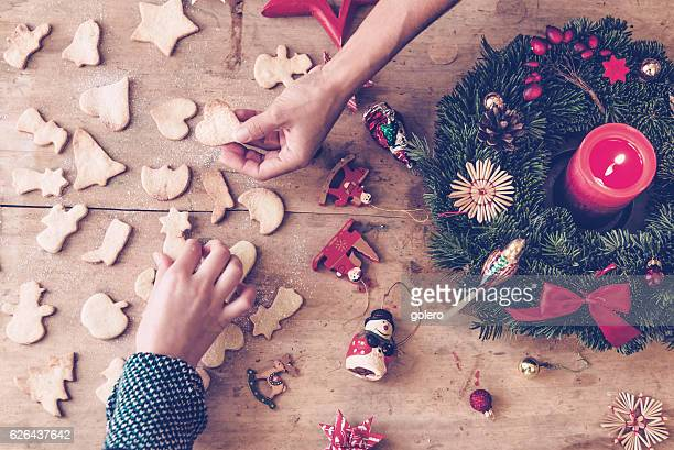 rustic wooden christmas table with hands holding selfmade cookies - adviento fotografías e imágenes de stock