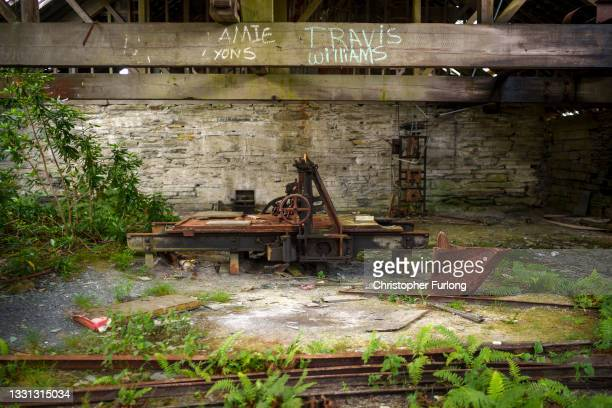 Rusting machinery is taken over by vegetation at the disused Maenofferen Slate Quarry on July 29, 2021 in Blaenau Ffestiniog, United Kingdom. The...