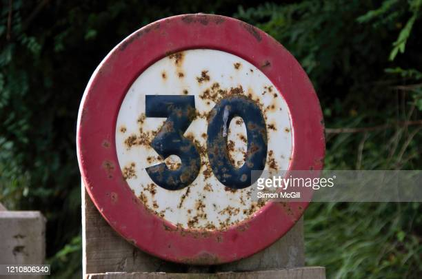 rusty  30 kilometre per hour speed limit sign on a mountain road - road sign board stock pictures, royalty-free photos & images