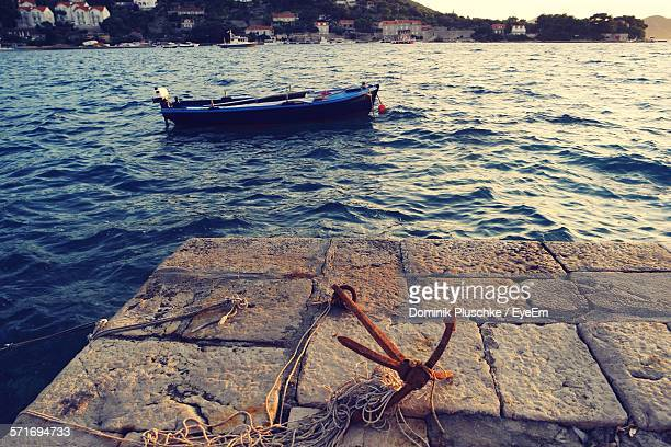 Rusty Anchor And Boat In Sea