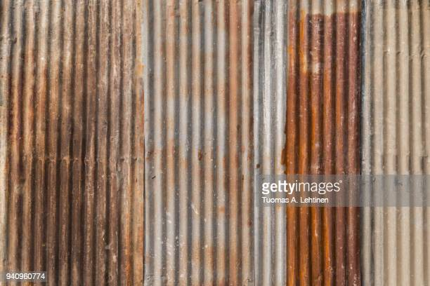 rusty and corrugated iron metal construction site wall texture background. - corrugated iron stock photos and pictures