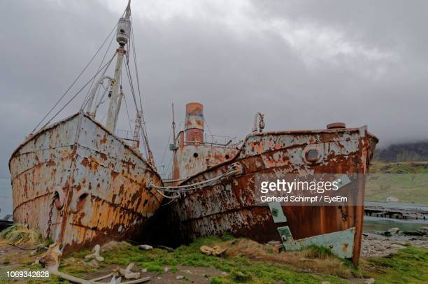 rusty boats on field against sky - gerhard schimpf stock pictures, royalty-free photos & images
