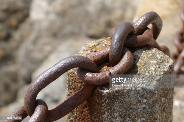 rusty chain on rock - chain stock pictures, royalty-free photos & images