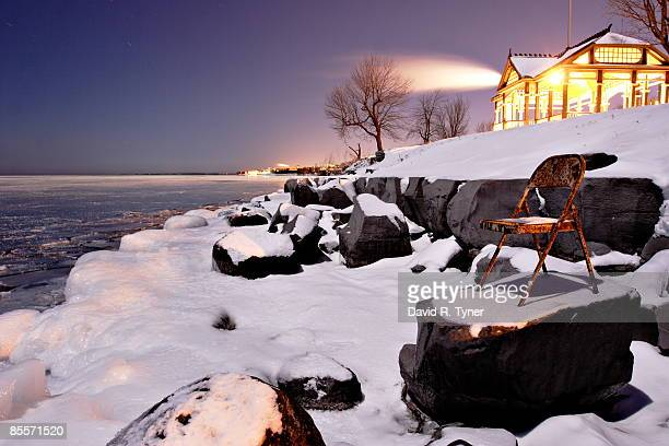 rusty chair on a snowy shoreline - kingston ontario stock photos and pictures