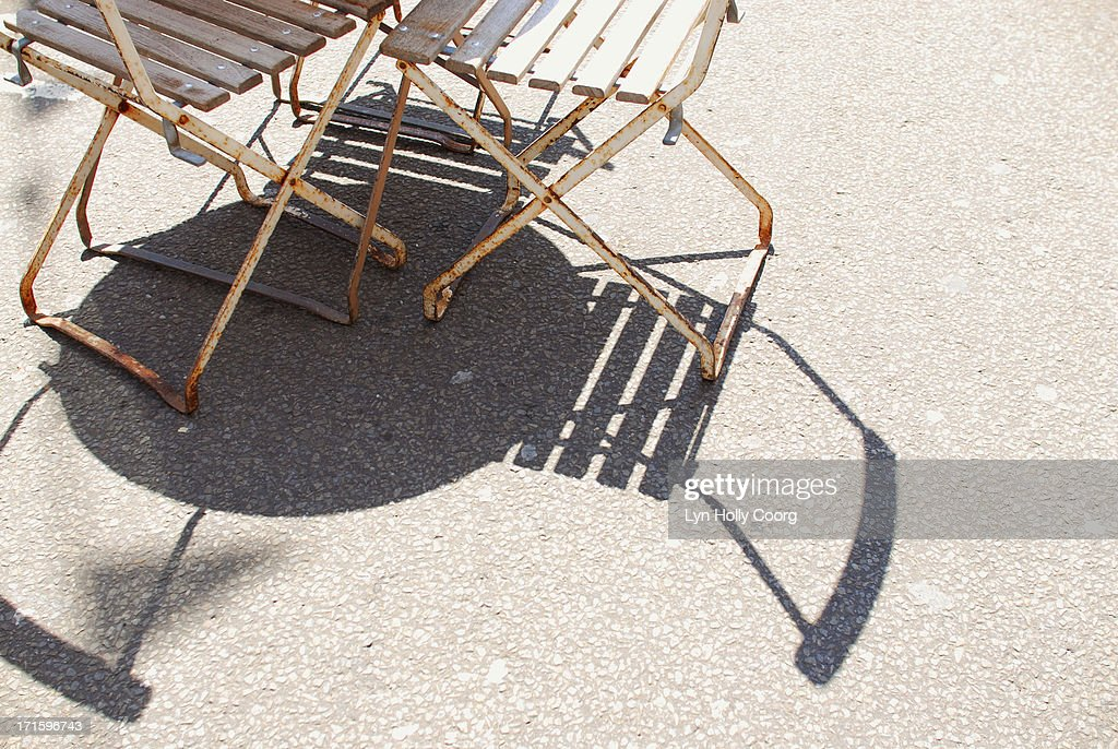 Rusty chairs and table casting shadows on ground : Stock Photo