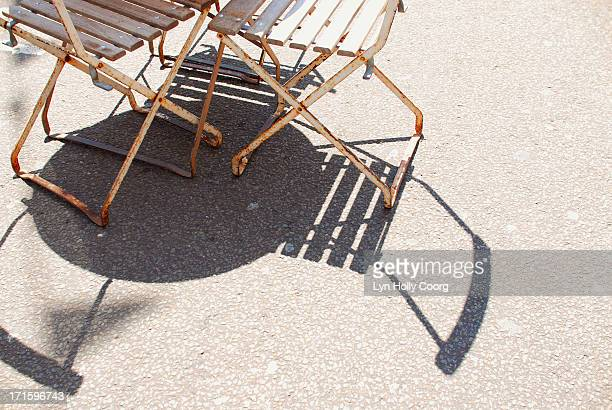 rusty chairs and table casting shadows on ground - lyn holly coorg stock photos and pictures
