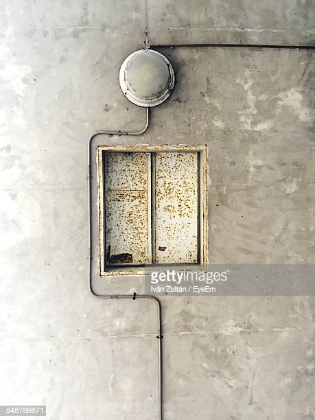 rusty closed window and electric light on wall - iván zoltán stock pictures, royalty-free photos & images