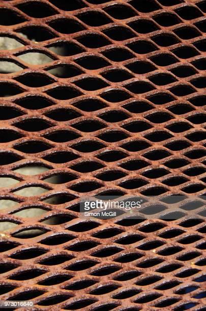rusty metal grate over a street drain - metal grate ストックフォトと画像