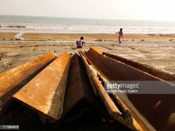 Rusty Metal Rods And Boys At Beach Against Clear Sky