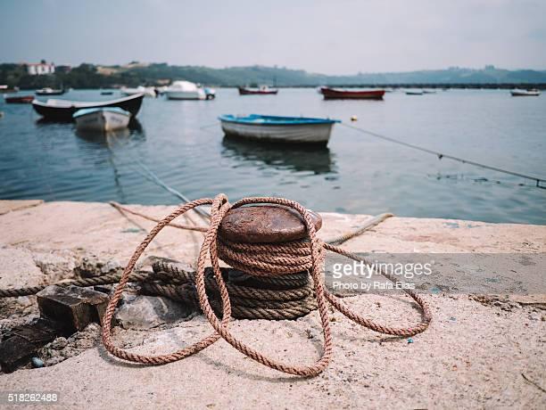 Rusty mooring bollard with ropes