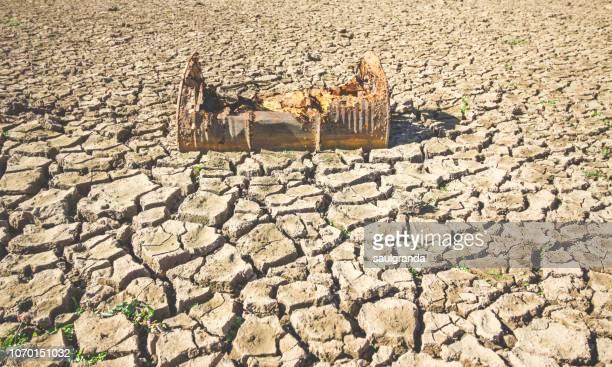 rusty oil drum over cracked and dried mud - erosionado fotografías e imágenes de stock