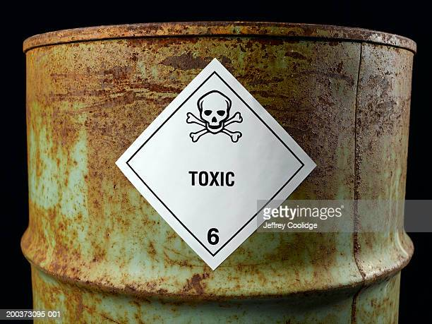 Rusty oil drum with toxic label, close-up