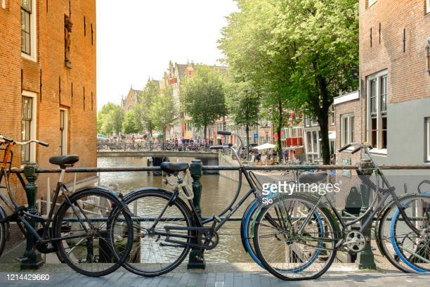 """rusty old bicycles on a bridge over a canal with traditional old canal houses in amsterdam, the capitol of the netherlands - """"sjoerd van der wal"""" or """"sjo"""" stock pictures, royalty-free photos & images"""