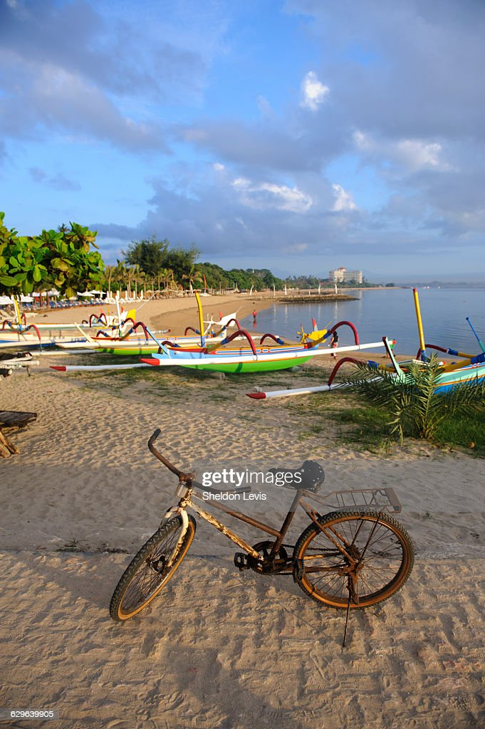 Rusty old bike on Balinese beach at sunrise : Stock Photo