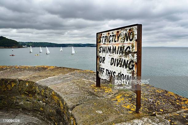 CONTENT] Rusty old sign stating no swimming or diving from this point with sailing bouts in background Taken at Saundersfoot harbour in Pembrokeshire...