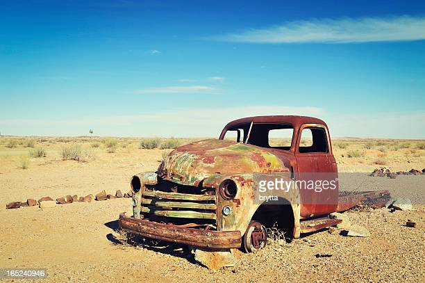 rusty old wreck abandoned in the namibia desert - abandoned car stock photos and pictures