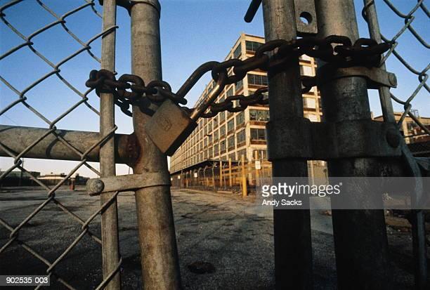 rusty padlock and chain on gates of closed automobile plant - sluiten stockfoto's en -beelden