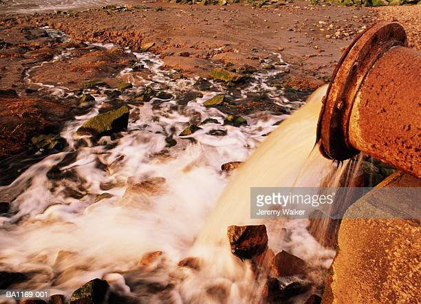 rusty pipe pumping effluent onto river bank - 水質汚染 ストックフォトと画像
