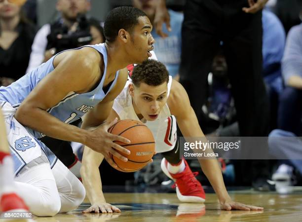 Rusty Reigel of the Davidson Wildcats tries to stop Garrison Brooks of the North Carolina Tar Heels during their game at Spectrum Center on December...