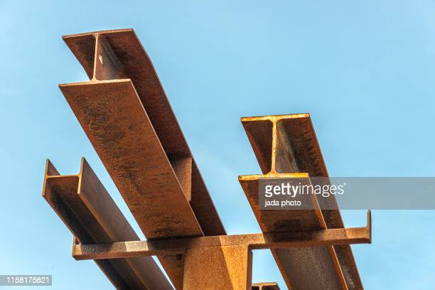 rusty steel beams placed outside on a steel rack - stahl stock-fotos und bilder