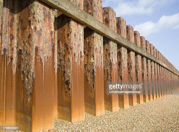 Rusty steel piling sea wall defenses and shingle beach near Bawdsey Quay Suffolk England