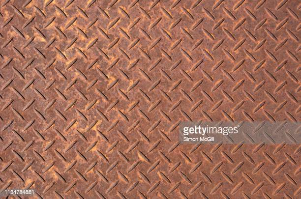 rusty steel plate with cross-hatch non-slip texture pattern - ugly wallpaper stock photos and pictures