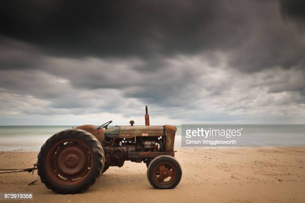 Rusty tractor on beach, Norfolk, England, UK