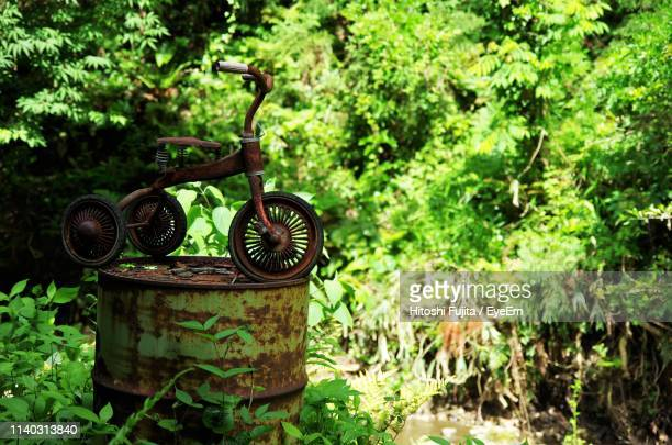 Rusty Tricycle On Old Metallic Barrel In Forest