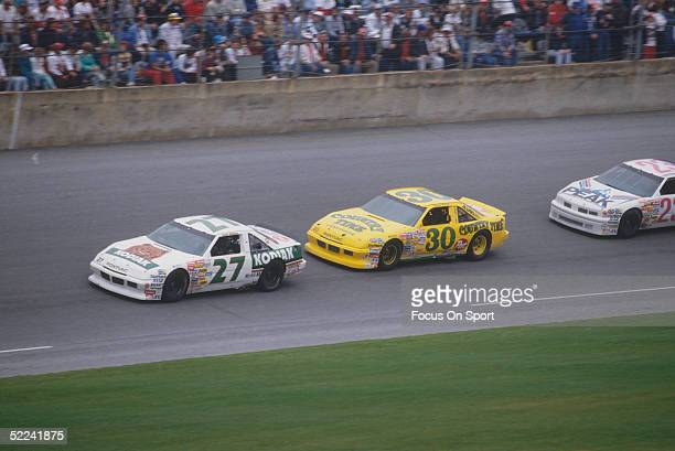 Rusty Wallace leads the race around a turn in his Kodiak car against the Michael Waltrip Country Time car during the Daytona 500 at the Daytona...