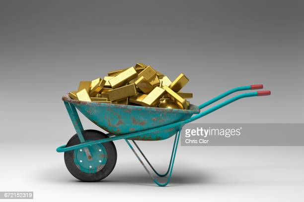 rusty wheelbarrow full of gold bars - wheelbarrow stock photos and pictures